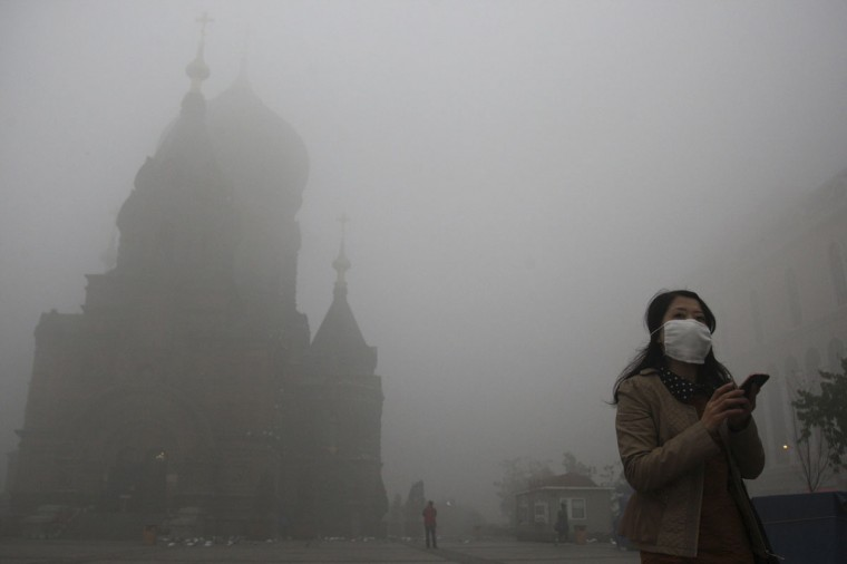A woman wearing a mask checks her mobile phone during a smoggy day on the square in front of Harbin's landmark church. (Reuters photo)
