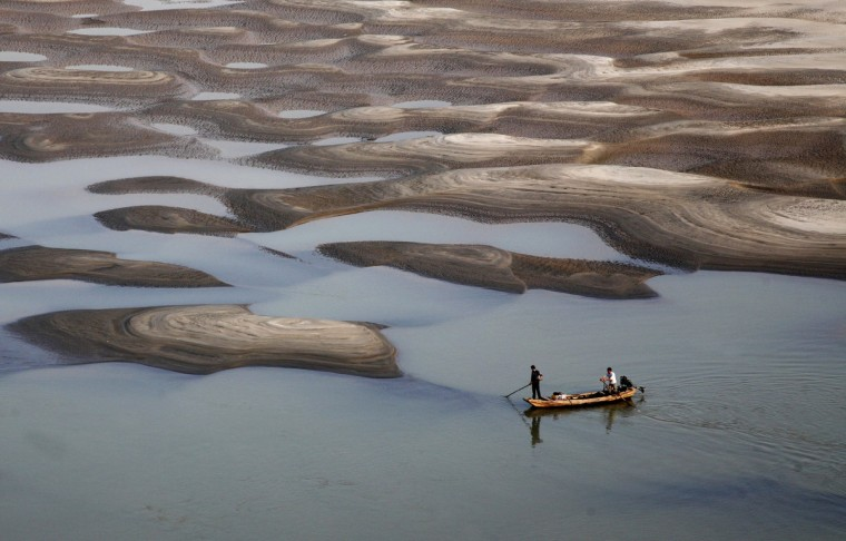 Two men row a boat past a partially dried-up riverbed on a section of the Yangtze River in Jiujiang, Jiangxi province. (Reuters)