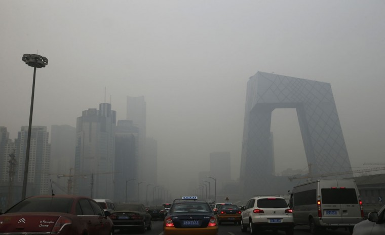 Cars travel on a road amid heavy haze in Beijing on February 21, 2014. (REUTERS/Kim Kyung-Hoon)