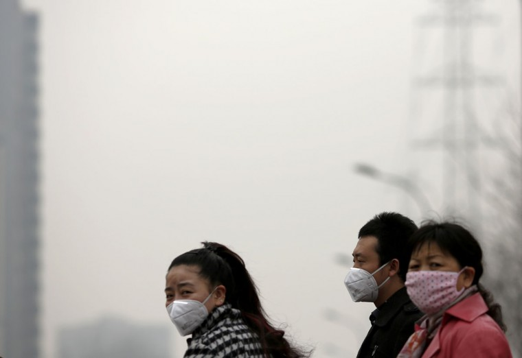 People wearing masks wait for a taxi amid the heavy haze in Beijing on February 22, 2014. (REUTERS/Kim Kyung-Hoon)