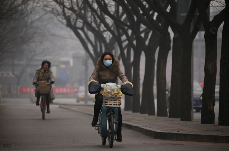 A woman wearing a mask rides an electric bicycle along a street on a hazy afternoon in Beijing on February 24, 2014. (REUTERS/Petar Kujundzic)