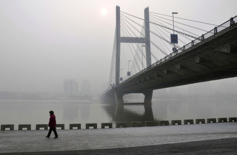 A resident walks along a street on the banks of the Songhua River near a highway bridge on a hazy day in Jilin, Jilin province on February 25, 2014. (REUTERS photo)