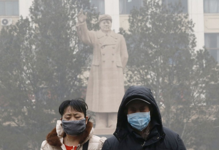 People wearing masks walk past a statue of late Chinese Chairman Mao Zedong in Beijing on February 26, 2014. (REUTERS/Kim Kyung-Hoon)