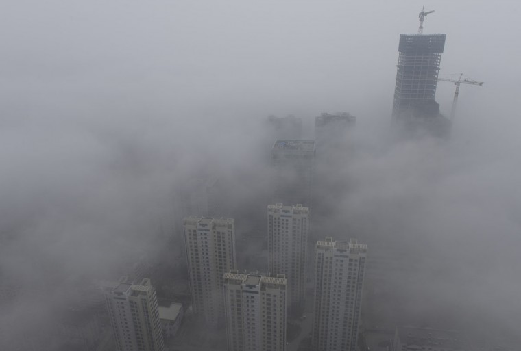Buildings are seen shrouded in heavy haze at Qingdao development zone, Shandong province, on February 25, 2014. (Reuters photo)