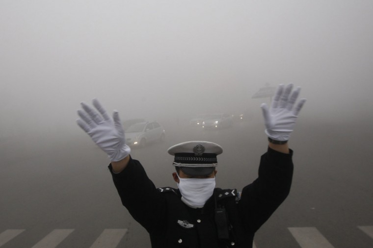 A traffic policeman signals to drivers during a smoggy day in Harbin. The second day of heavy smog with a PM 2.5 index forced the closure of schools and highways, exceeding 500 micrograms per cubic meter Monday morning in downtown Harbin, according to Xinhua News Agency. (Reuters photo)