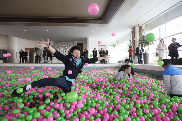 "A man jumps in a swimming pool filled with pink and green plastic balls during a Guinness World Records attempt of the Largest Ball Pit as part of the ""Pink October"" campaign at Kerry Hotel in Pudong, (Aly Song/Reuters)"