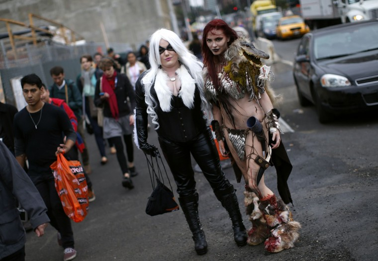 Nicci Fette (R), dressed as comic book character Red Sonja, and Courtney Rose (L), dressed as Red Cat, pose for a photograph at New York's Comic-Con convention. (Mike Segar/Reuters)