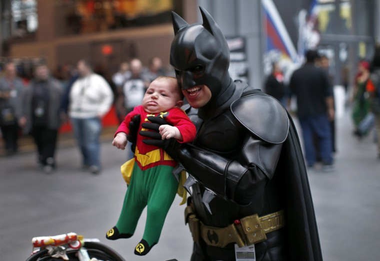A man in a Batman costume holds up an infant dressed as Robin at New York's Comic-Con convention. (Mike Segar/Reuters)