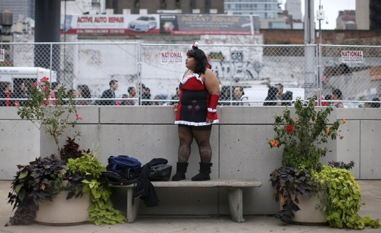 Kimberly Rosa from New York City dressed as comic series character Harlequin stands on a bench as she looks for her friends at New York's Comic-Con convention. (Mike Segar/Reuters)