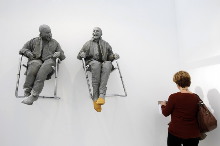 """A visitor looks at """"2 Seated on the Wall with Big Chairs"""" art works by artist Juan Munoz during the International Contemporary Art Fair (FIAC) at the Grand Palais in Paris. The International Contemporary Art Fair (FIAC) will run from October 24 to 27 in the French capital. (Benoit Tessier/Reuters)"""