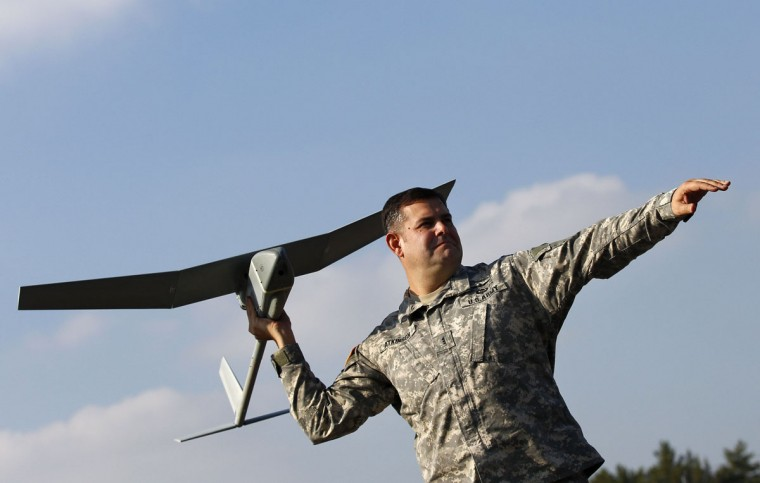 """U.S. soldier Randell Atkinson poses in the starting position with a """"Raven"""" drone during its official presentation by the German and U.S. Unmanned Aerial Systems (UAS) at the U.S. military base in Vilseck-Grafenwoehr October 8, 2013. (Michaela Rehle/Reuters)"""