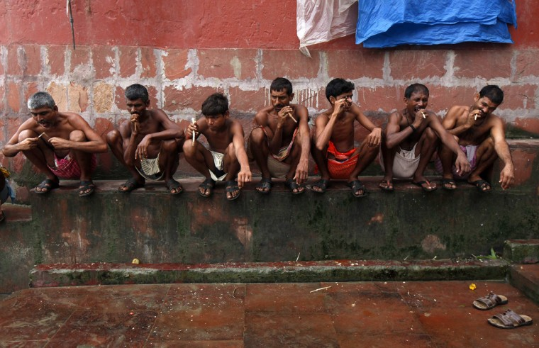 Labourers brush their teeth with neem twigs on the banks of the Ganges river in Kolkata. (Rupak De Chowdhuri/Reuters)