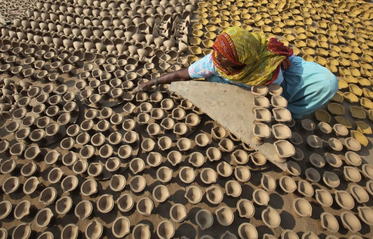 A woman puts out earthen lamps to dry in the sun at her workshop ahead of the Hindu festival of Diwali in the northern Indian city of Chandigarh. Earthen lamps are sold in large numbers during Diwali, the annual Hindu festival of lights, as people use them to decorate their homes. The Diwali festival will be observed this year on November 3. (Ajay Verma/Reuters)