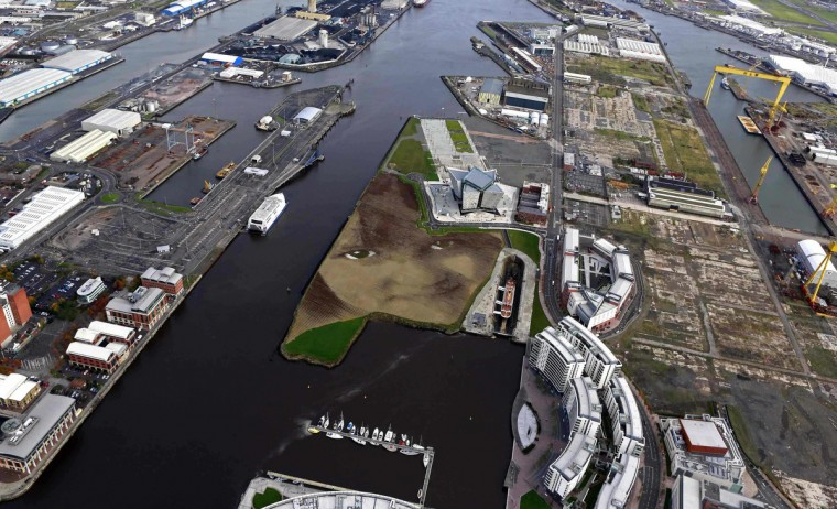 """A piece of land art entitled """"Wish"""" showing the face of an anonymous six-year-old local Belfast girl is seen in this aerial view of the Titanic quarter in Belfast October 23, 2013. The artwork by Cuban-American artist Jorge Rodriguez-Gerada spans 11 acres, is made up from 2,000 tonnes of sand, 2,000 tonnes of soil and some 30,000 wooden pegs. It will remain on view until December 2013. (Cathal McNaughton/Reuters)"""