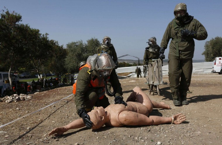 An Israeli soldier from the home front command wearing protective gear kneels next to a dummy during a drill simulating a chemical attack in the town of Beit Shemesh, near Jerusalem. (Baz Ratner/Reuters)