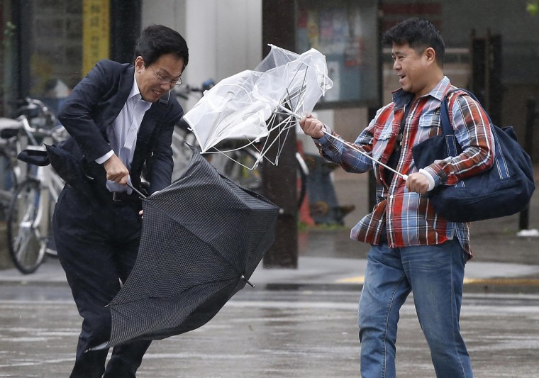 Men react as they struggle against strong wind and rain caused by approaching Typhoon Wipha at a business district in Tokyo. (Toru Hanai/Reuters photo)