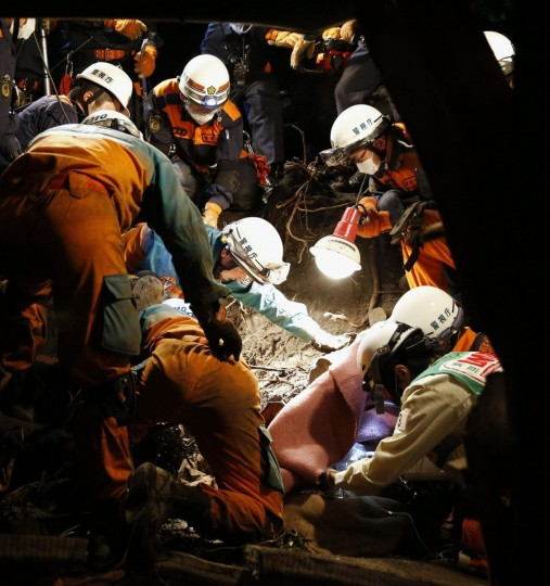 Rescue workers save a woman who survived a landslide caused by Typhoon Wipha on Izu Oshima island, south of Tokyo, in this photo taken by Kyodo. A typhoon killed 17 people in Japan on Wednesday, most on an offshore island, but largely spared the capital and caused no new disaster as it brushed by the wrecked Fukushima nuclear power station, the plant's operator said. (Kyodo/Reuters)