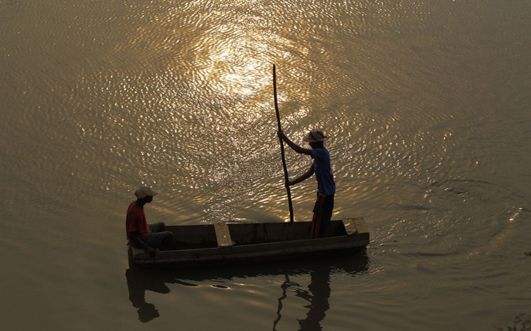 Men paddle a boat across the Ikopa river in Madagascar's capital Antananarivo. Voters in Madagascar's presidential election on Friday desperately hope for an end to a five-year political crisis that has scared off investors and severely damaged the economy, but there is little optimism they will get their wish. (Thomas Mukoya/Reuters)