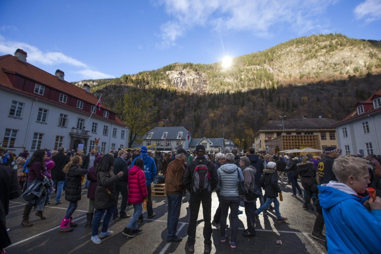 People gather during the official opening of giant sun mirrors (top) erected on the mountainside, in the town of Rjukan. The town, surrounded by mountains high enough to deprive its inhabitants of direct sunlight during winter, would be able to receive sunlight in the central square from deflected sun rays from the mirrors. (Terje Bendiksby/NTB Scanpix)