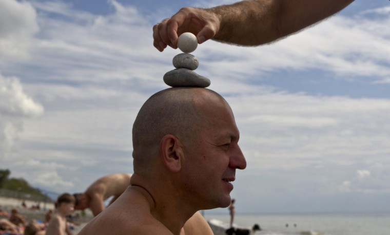 "Engineer Yuri erects a stone pyramid on the head of his acquaintance and colleague Alexander as they rest on the beach in the Adler district of Sochi. With just months to go before Russia is due to host the 2014 Winter Olympics in the Black Sea resort of Sochi, cranes still tower over muddy construction sites in the palm tree-lined city, as it tries to complete its multi-billion dollar transformation into a winter sports hub. If everything goes according to plan the Games will be a showcase for Russia's achievements under President Vladimir Putin, the culmination of a six-year personal project on a truly Soviet scale. But the President's dream could still be crushed if Sochi is not ready on time, protests break out over a Russian law banning ""gay propaganda"" or Islamist militants attack the Games. Picture taken September 22, 2013. (Maxim Shemetov/Reuters)"