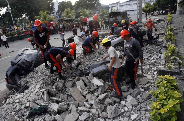 Rescuers clear debris from buried vehicles after an earthquake struck Cebu city, in central Philippines. (Erik De Castro / Reuters photo)