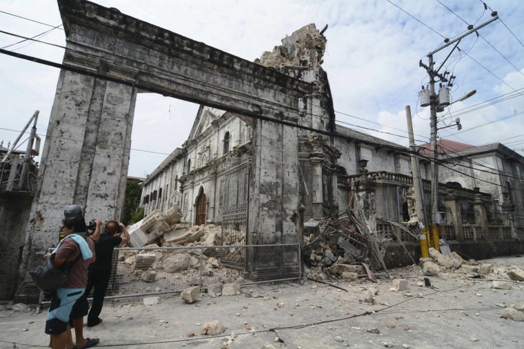Local photographers takes pictures of the damage to the historic Basilica Minore of Santo Nino de Cebu after an earthquake hit the church in Cebu City, central Philippines. (Reuters photo)