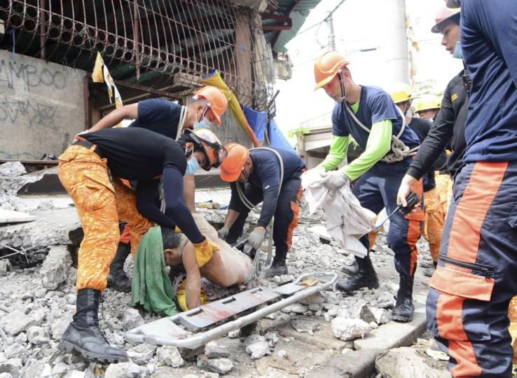 Rescuers retrieve a body from the debris at a fishing port that was damaged after a earthquake struck Cebu city, central Philippines. (Reuters photo)