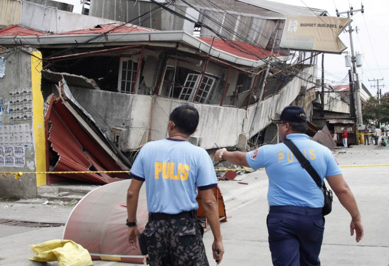 Police investigators inspect a collapsed building after an earthquake struck Cebu city, central Philippines. (Reuters photo)