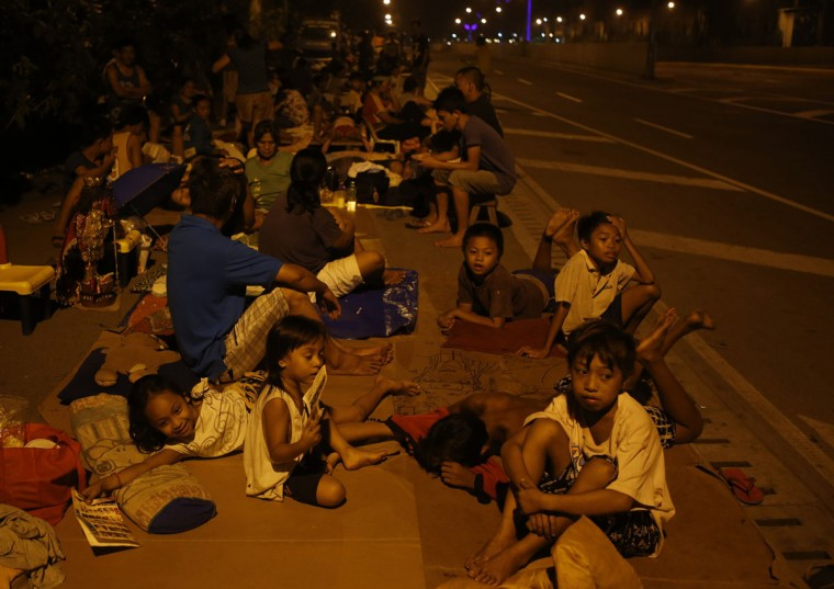 Residents rest on a sidewalk as they spend the night on a road due to aftershocks from an earthquake in Cebu city, central Philippines. (Erik De Castro / Reuters)