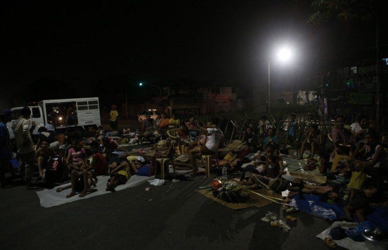 Residents spend the night on a road due to aftershocks from an earthquake in Cebu city, central Philippines. (Erik De Castro / Reuters)