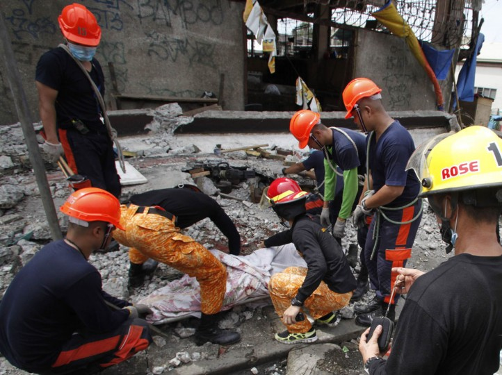 Rescuers retrieve a body killed in a fish market after an earthquake struck Cebu city, in central Philippines. (Charlie Saceda / Reuters)