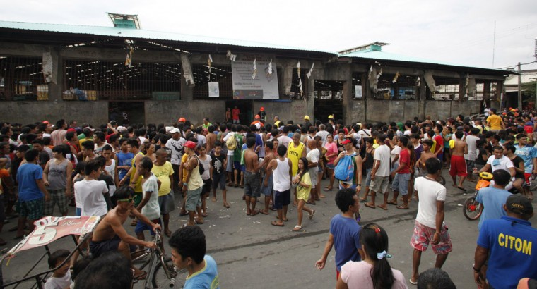 Residents gather outside a fish market after an earthquake struck Cebu city, in central Philippines. (Charlie Saceda / Reuters)