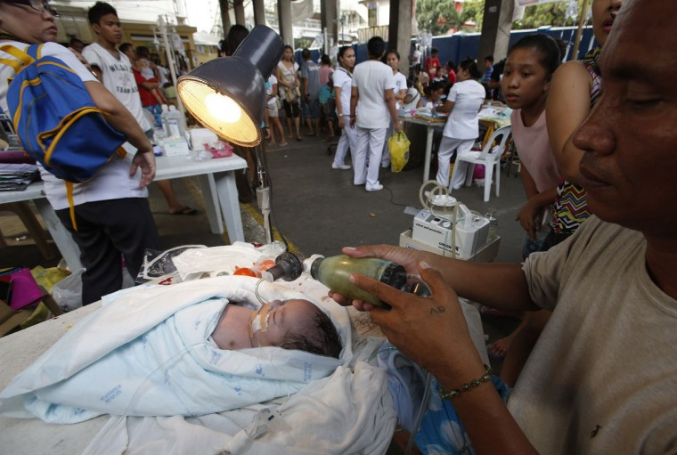 A man pumps oxygen to his newborn baby boy after hospital patients were evacuated from earthquake stricken Cebu city, in central Philippines. (Erik De Castro / Reuters)