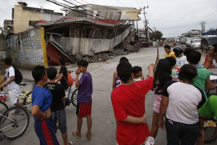 Residents stand outside a damaged building after an earthquake struck Cebu city, in central Philippines. (Erik De Castro / Reuters)