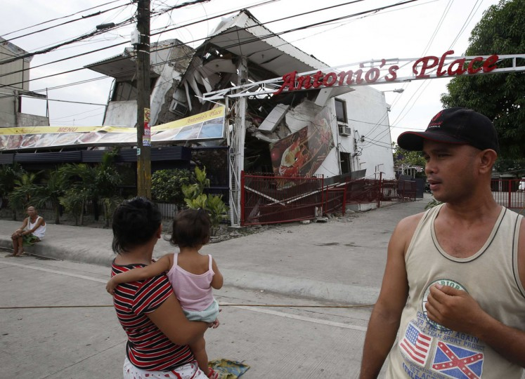 Residents stand outside a damaged house after an earthquake struck Cebu city, in central Philippines. (Erik De Castro / Reuters)