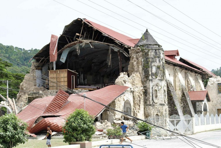 Residents walk past the collapsed facade of the San Pedro y San Pablo Parish after an earthquake struck Loboc town, Bohol province, central Philippines. (Reuters photo)