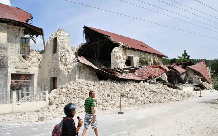 Residents walk past the collapsed wall of the San Pedro y San Pablo Parish after an earthquake struck Loboc town, Bohol province, central Philippines. (Reuters photo)