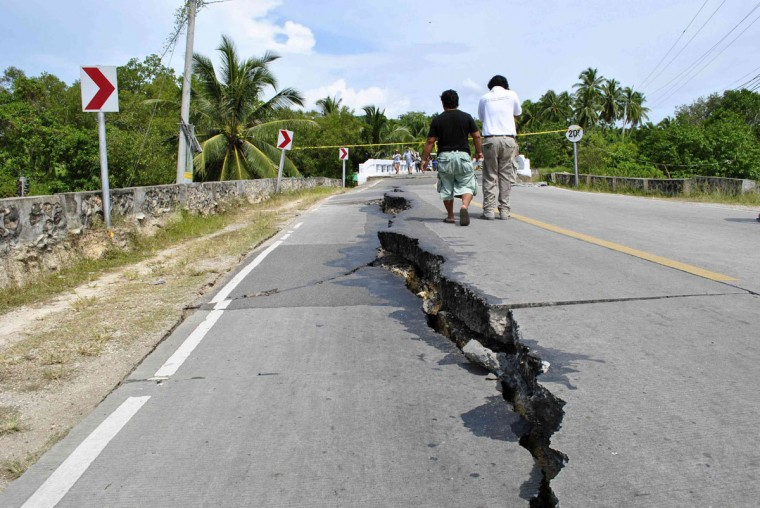 Residents walk along huge cracks in a road after an earthquake struck Bohol province, central Philippines. (Reuters photo)