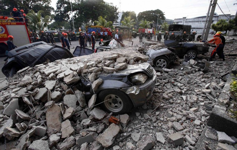 Firefighters stand near destroyed vehicles covered with rubble after an earthquake struck Cebu city, in central Philippines. (Erik De Castro / Reuters)