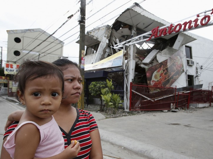 A woman carries her daughter outside a damaged house after an earthquake struck Cebu city, in central Philippines. (Reuters photo)