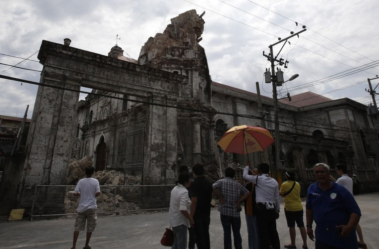 Church officials stand outside a damaged centuries-old Basilica Minore of Sto Nino de Cebu church after an earthquake struck Cebu city, in central Philippines. (Erik De Castro / Reuters)