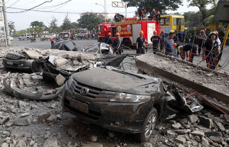 Firefighters stand near damaged vehicles after an earthquake struck Cebu city, in central Philippines. (Erik De Castro / Reuters)