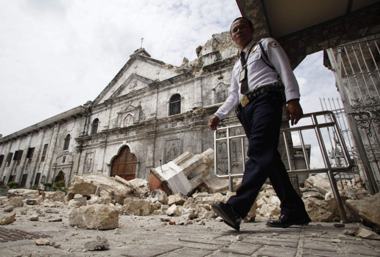 A security guard walks past the bell tower church of historic Basilica Minore of Sto Nino that fell down after an earthquake hit Cebu city, central Philippines. (Reuters photo)