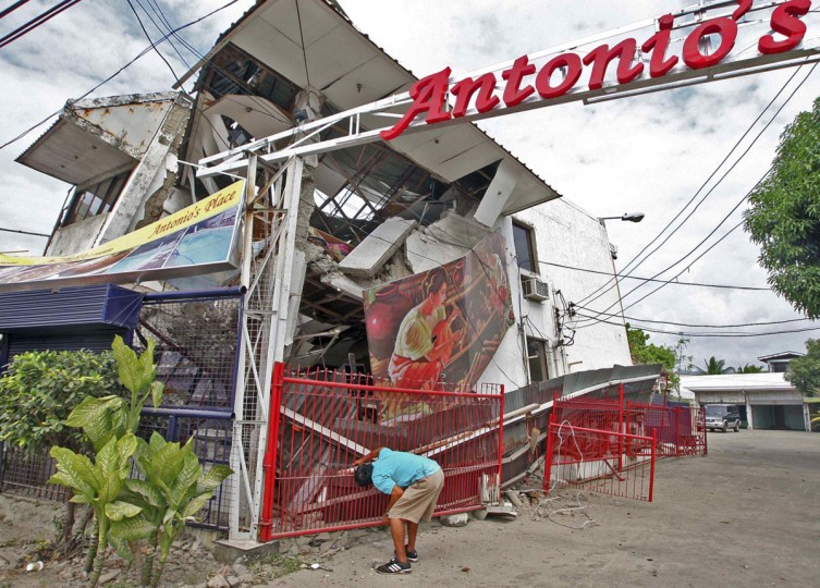 A resident inspects a building collapsed during an earthquake in Cebu city, central Philippines. (Reuters photo)
