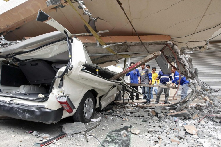 Residents inspect a car after a concrete block fell on it during an earthquake in Cebu city, central Philippines. (Reuters photo)