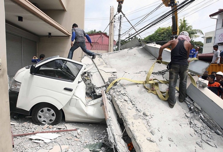 Workers use a crane to lift up concrete block that fell on a car after buildings collapsed during an earthquake in Cebu city, central Philippines. (Reuters photo)