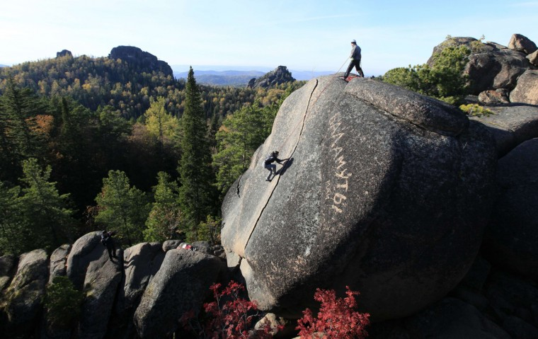 "A tourist climbs up to reach the top of the rock named ""The Fourth Stolb"" (the Fourth Pillar) at the Stolby national nature reserve in the Siberian Taiga area outside the Russian city of Krasnoyarsk. Picturesque rocky blocks rising above the Taiga draw attention of tourists from all over Russia and abroad.(Ilya Naymushin/Reuters photo)"