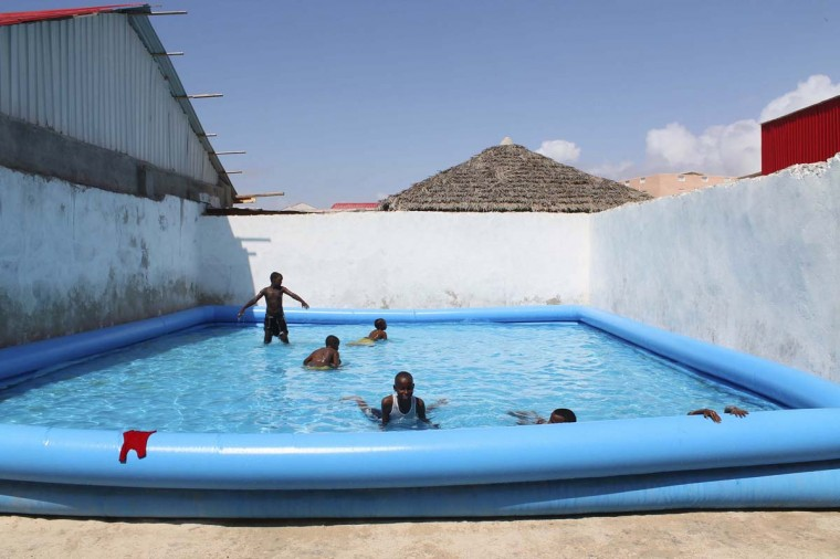 Children play in a swimming pool at a guest hotel in Mogadishu October 16, 2013. Street lamps now brighten some of Mogadishu's battle-scarred roads and couples hold hands at the seaside next to bombed-out beachfront buildings, a scene that would have been unthinkable when the Islamist al Shabaab group held sway here. However, rebuilding a life many in the world take for granted is a slow process after more than 20 years of civil war and anarchy in Somalia. Islamists, who control swathes of countryside and some towns, have launched several attacks in Mogadishu, and last month they showed their reach, claiming responsibility for a deadly attack on a Kenyan shopping mall. (Feisal Omar/Reuters)