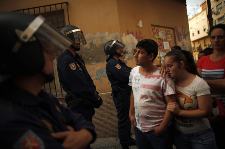 A couple stand in front of Spanish riot police after they were evicted from an unoccupied building of flats in Malaga, southern Spain. A total of 13 families, included 12 children, had occupied the building since February. Members from various support platforms failed to stop the eviction and three activists were arrested when they refused to leave the roof of building, according to local media. (Jon Nazca/Reuters photo)