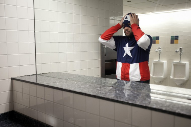 A man dressed as Captain America adjusts his mask after washing his hands in the bathroom at ComicCon in New York. (Carlo Allegri/Reuters)